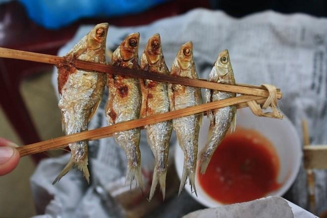 Cá nướng sông Đà: Những con cá tươi rói để nguyên con rồi dùng xiên từ đầu tới đuôi, dùng nẹp kẹp vào để cá khỏi bị rơi. Cá được nướng trên than hồng cho đến khi cháy xém, tỏa mùi thơm. Khi ăn chỉ cần rắc thêm một chút muối, rồi quấn vào trong lá chuối để một lúc là có thể ăn được. Ảnh: Danviet.